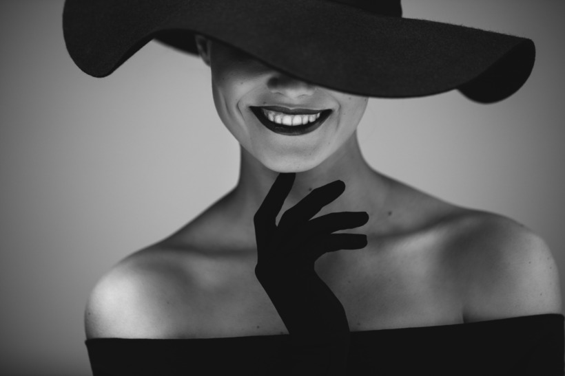 Elegant beautiful woman in a black dress and hat
